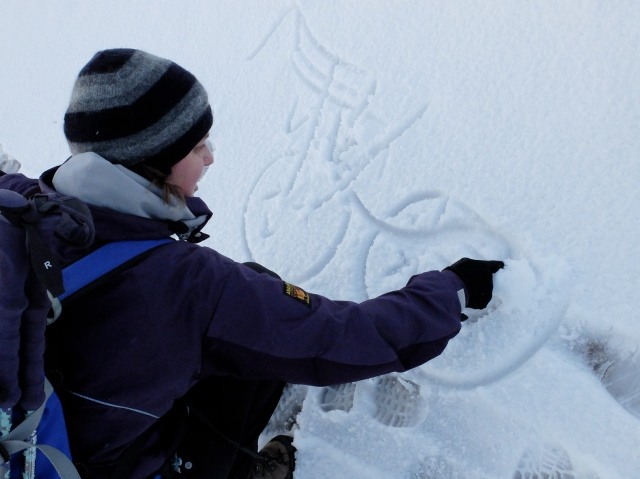 Alison Austin of the John Muir Trust drawing a diagram in the snow of Ben Nevis to explain the mountain's unique geology