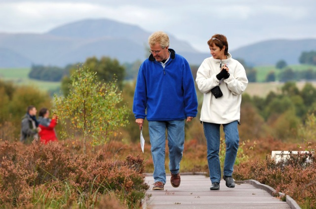 Visitors on the boardwalk trail at Flanders Moss NNR,