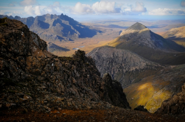 Cresting the rocky wave of Bla Bheinn with views to the Cuillins, Isle of Skye