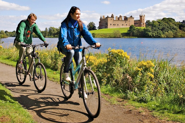 Cycling on footpath past Linlithgow Palace and loch. ©beckyduncanphotographyltd.