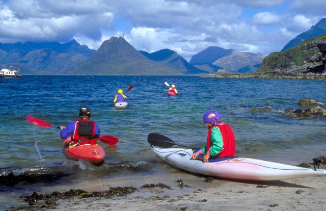 Kayakers take to the sea from Elgol, Isle of Skye, to explore a varied coastal and mountain landscape created by 58 million year old volcanic rocks intruding older sedimentary layers. © George Logan/SNH