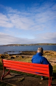 man in blue jacket sitting on red bench, watching sailing boats on the Firth of Clyde