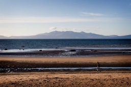 man running along beach at Ardorssan, with hills of Arran in background